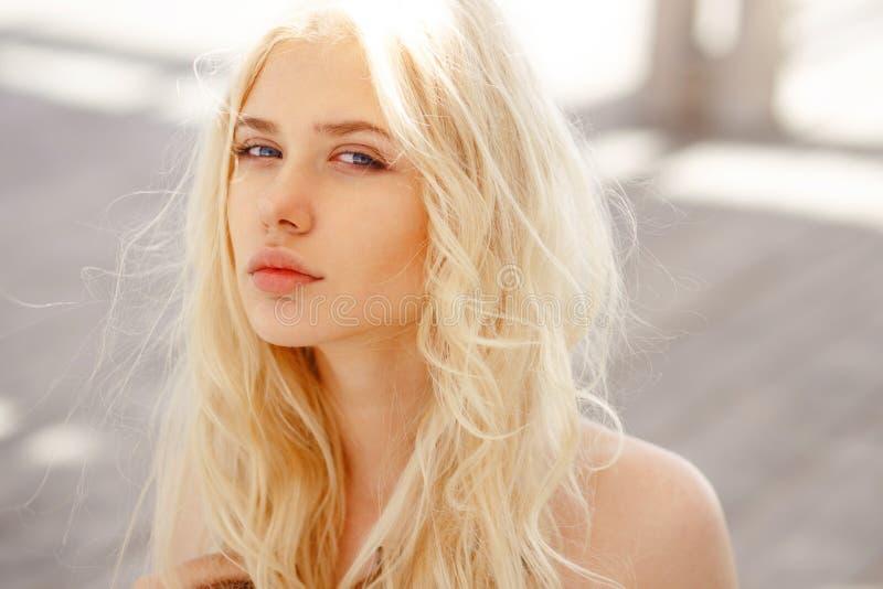 Het leuke blonde met engelachtige blauwe ogen, het krulhaar en de grote lippen bekijken onschuldig camera, isoalted op een houten stock afbeelding