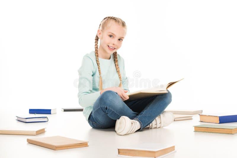 het leuke boek van de meisjelezing en het glimlachen bij camera royalty-vrije stock afbeeldingen