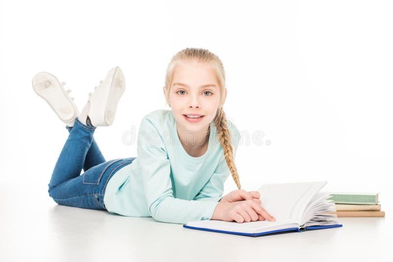 het leuke boek van de meisjelezing en glimlachen bij camera terwijl het liggen stock fotografie