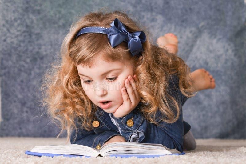 Het leuke boek van de meisjelezing terwijl het liggen op vloer stock foto