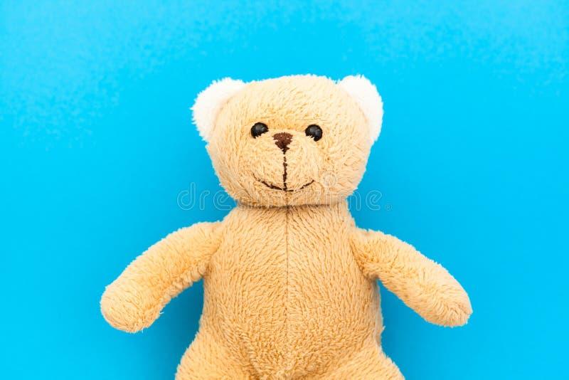 Het leuke bruine stuk speelgoed van het teddybeerkind met zichtbaar hoger lichaam en open die wapens in een naadloze blauwe coulo royalty-vrije stock foto's