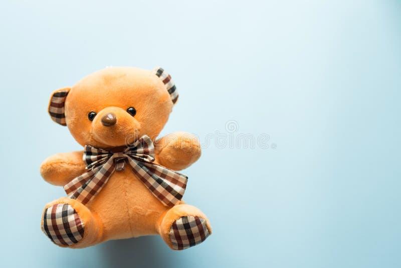 Het leuke bruine stuk speelgoed van het teddybeerkind met zichtbaar hoger lichaam en open wapens op blauwe achtergrond met exempl stock afbeelding
