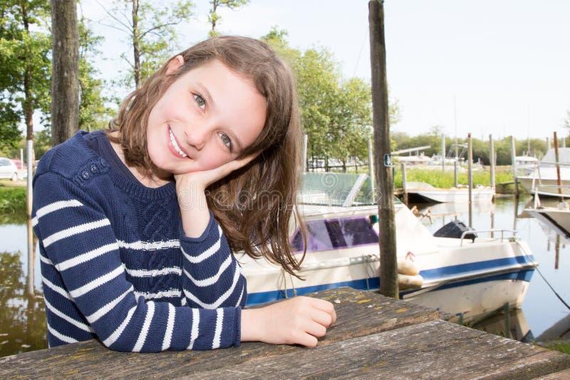 Het leuke close-up van het liitlemeisje tijdens vakantie dichtbij meerrivier en boot royalty-vrije stock foto's