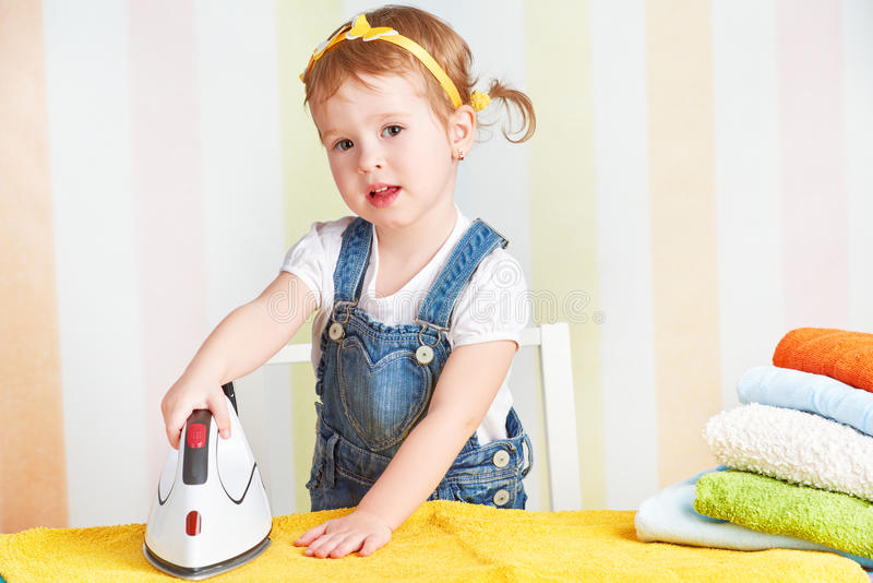 Het leuke de huisvrouwenijzer van het babymeisje kleedt ijzer, is bezig geweest met koepels royalty-vrije stock afbeelding