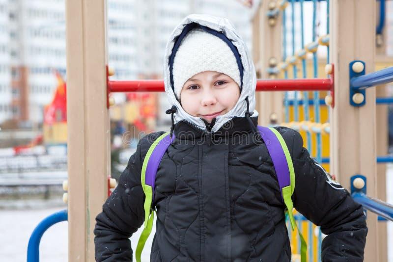 Het leuke Europese meisje in de winter kleedt tribunes op kinderenspeelplaats, gezwollen jasje met wolhoed en kap royalty-vrije stock foto's