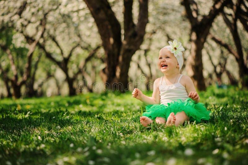 Het leuke gelukkige babymeisje lopen openlucht in de lentetuin stock afbeeldingen