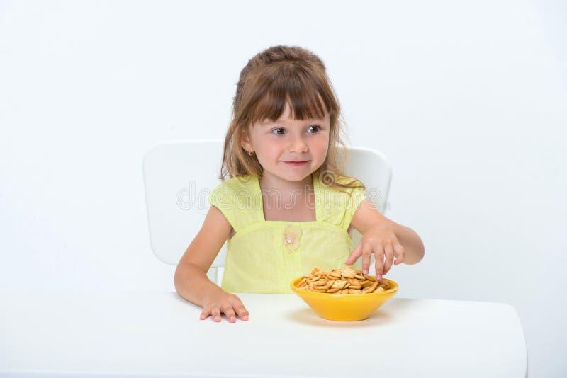 Het leuke gelukkige glimlachende emotionele en positieve meisje 3 éénjarigen in gele t-shirt die graangewas eten die schilfert bi stock foto's