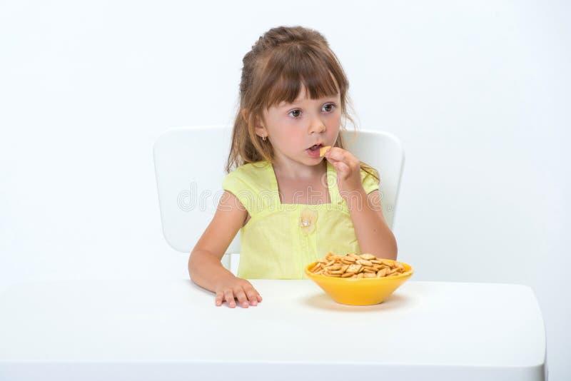 Het leuke gelukkige glimlachende emotionele en positieve meisje 3 éénjarigen in gele t-shirt die graangewas eten die schilfert bi stock afbeelding