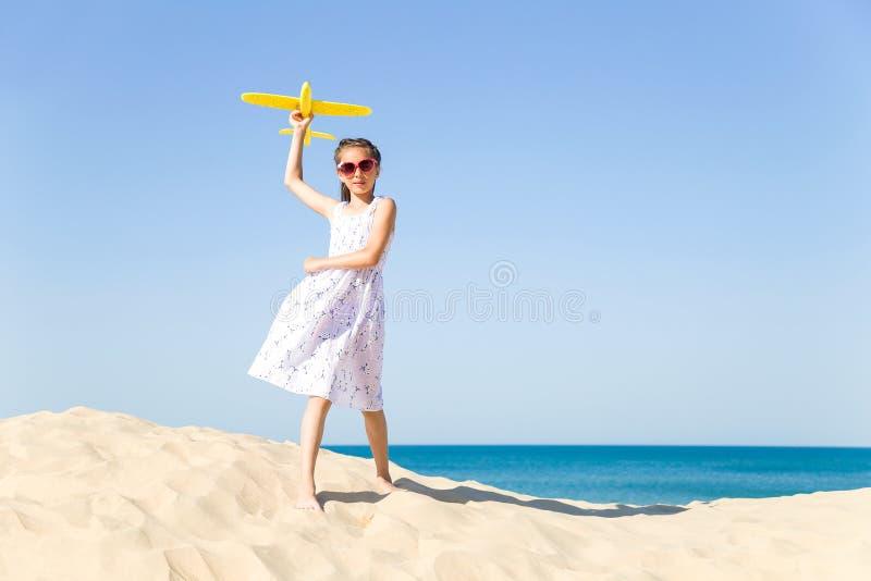 Het leuke gelukkige meisje zonoogglazen dragen en een wit die kleden het evolueren in wind het spelen met het geel royalty-vrije stock foto