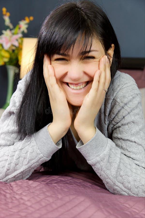 Het leuke gelukkige vrouw glimlachen die camera die in bed liggen kijken royalty-vrije stock foto's
