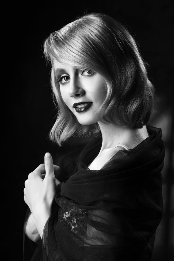 Het leuke gezicht die blond meisje met uitstekend stijlkapsel glimlachen, die een gouden fonkelende kleding en een zwarte sluier  stock afbeelding