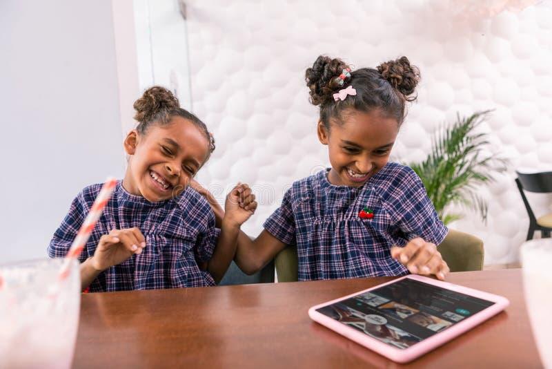 Het leuke het glimlachen dochters spelen bedriegt terwijl het hebben van ontbijt in cafetaria stock fotografie