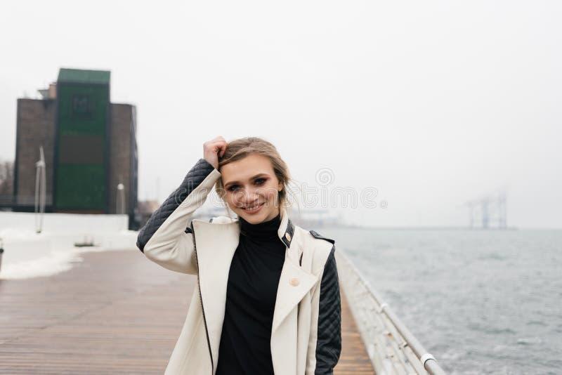 Het leuke het glimlachen meisje stellen dichtbij het overzees stock foto