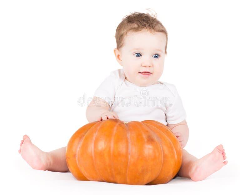 Het leuke grappige babymeisje spelen met een grote pompoen stock afbeelding