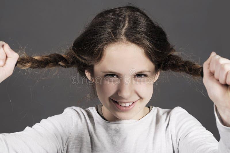 Het leuke grappige meisje scheurt haar haar met een reusachtige glimlach stock foto's