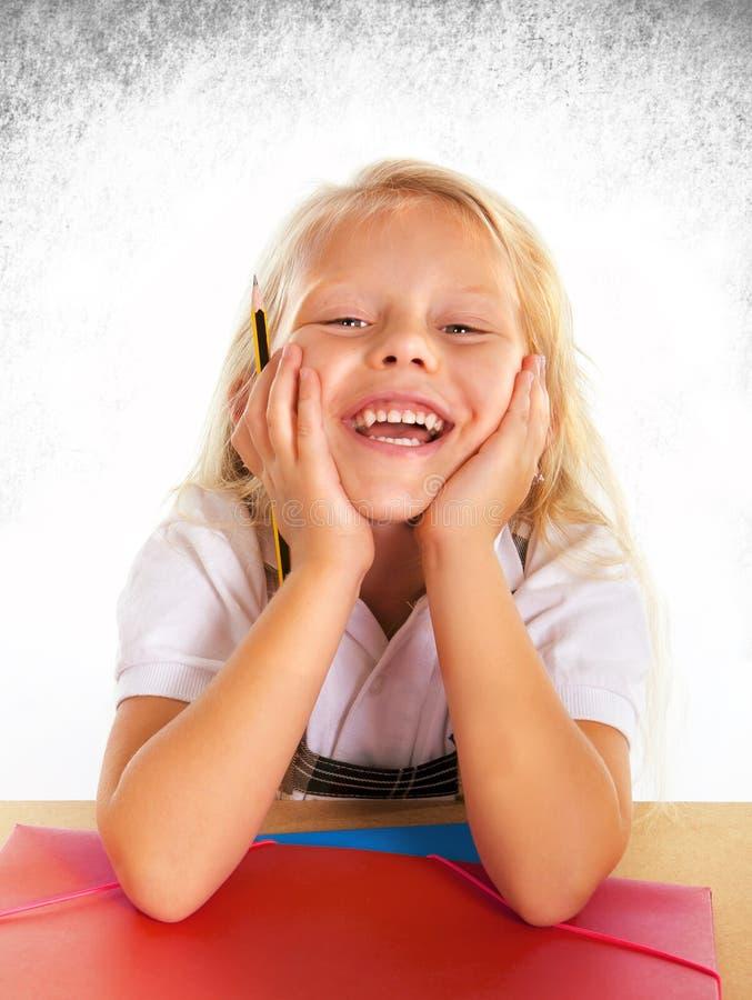 Het leuke haar van het schoolmeisjeblonde en het blauwe ogen glimlachen gelukkig op schoolbank royalty-vrije stock fotografie