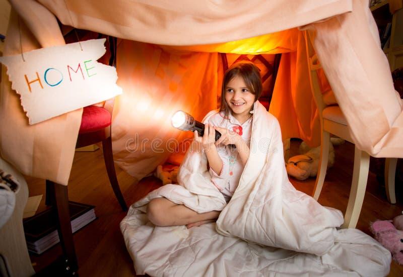 Het leuke het glimlachen meisje spelen met flitslicht dat binnenshuis van spatie wordt gemaakt royalty-vrije stock foto
