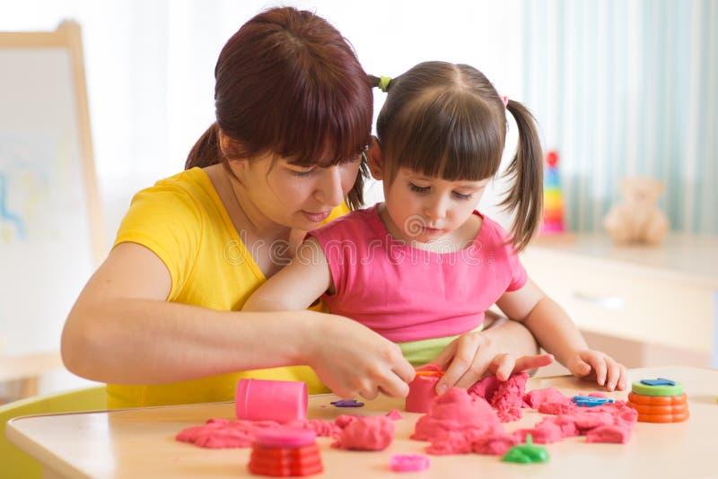 Het leuke jong geitje en moeder spelen met thuis het beeldhouwen van stuk speelgoed Meisje de bouwzandkasteel royalty-vrije stock fotografie