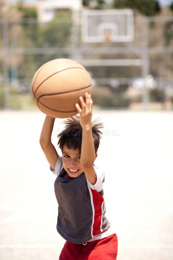Het leuke jonge basketbal van de jong geitjeholding stock foto's