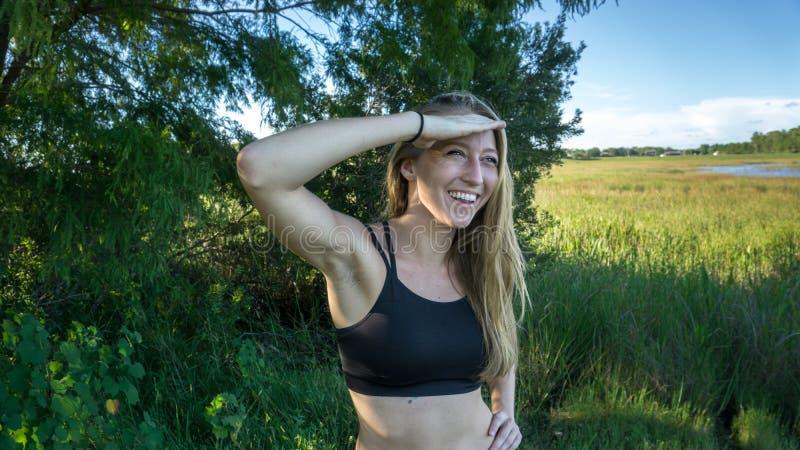 Het leuke jonge blondemeisje die met blauwe ogen ver weg in de afstand kijken met overhandigt haar hoofdgezicht lachend in bos stock afbeeldingen