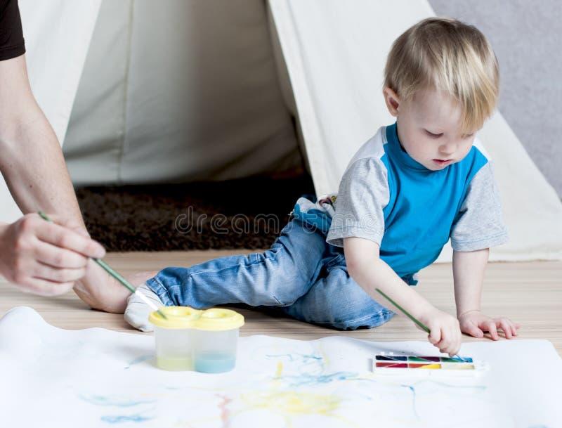 Het leuke jonge geitje met vader trekt een borstel op Witboek met watercolo royalty-vrije stock foto's