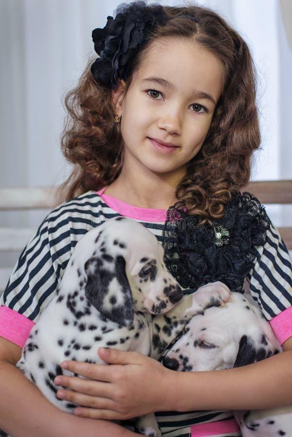 Het leuke jonge meisje spelen met puppy van dalmatian binnen Zij is bang stock afbeelding