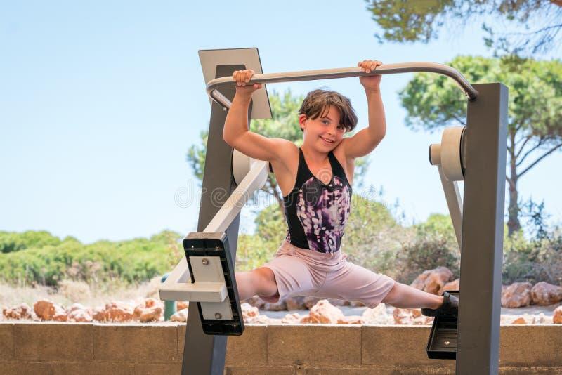 Het leuke jonge meisje uitoefenen, die de spleten op de dwarsmachine van de trainergymnastiek in openlucht doen stock afbeeldingen