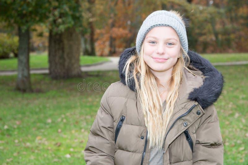 Het leuke jonge meisje van het tienerkind in de herfstpark stock foto's