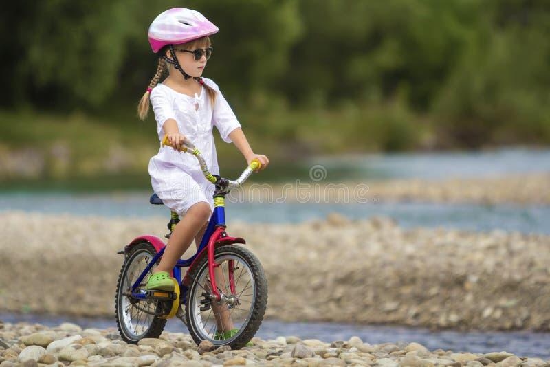 Het leuke jonge meisje in witte kleding, zonnebril met lange vlechten die roze berijdende het kindfiets dragen van de veiligheids royalty-vrije stock afbeeldingen