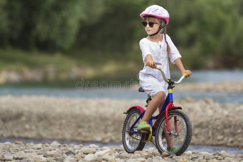 Het leuke jonge meisje in witte kleding, zonnebril met lange vlechten die roze berijdende het kindfiets dragen van de veiligheids stock afbeelding