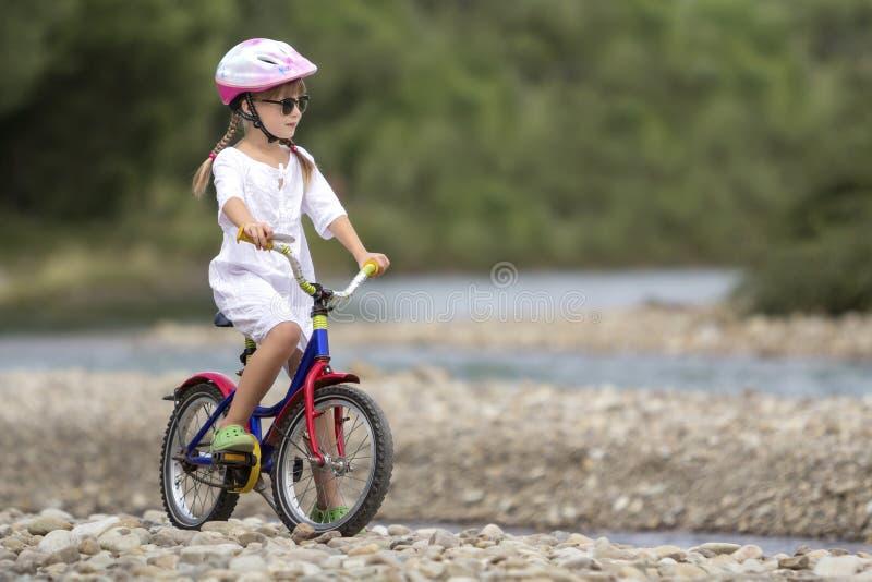 Het leuke jonge meisje in witte kleding, zonnebril met lange vlechten die roze berijdende het kindfiets dragen van de veiligheids stock foto's