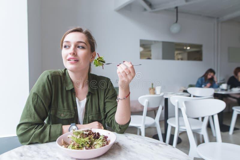 Het leuke jonge meisje zit in een comfortabel licht salade eten en restaurant die, die weg eruit zien royalty-vrije stock afbeelding