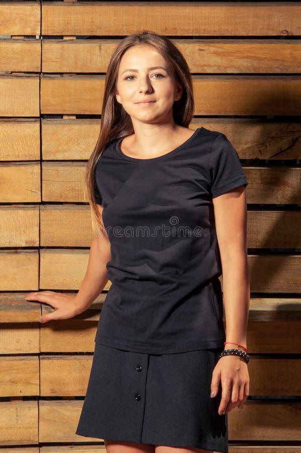 Het leuke jonge vrouw model stellen op houten omheiningsachtergrond royalty-vrije stock fotografie