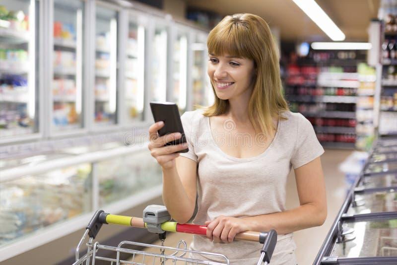 Het leuke jonge vrouw texting op haar celtelefoon in supermarkt stock foto