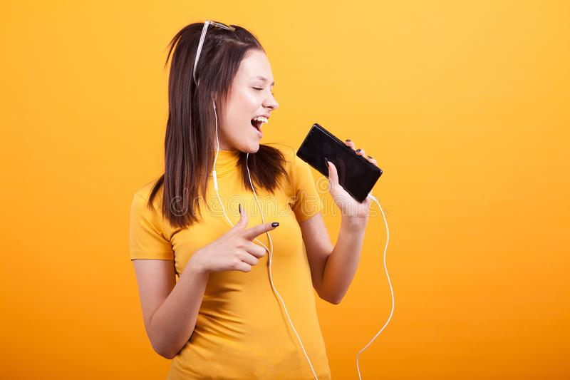Het leuke jonge vrouw zingen op haar telefoon en het richten royalty-vrije stock afbeelding