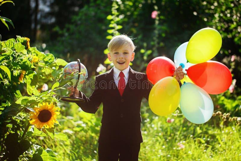 Het leuke jongen glimlachen, die naar school terugkeert Jongen in het kostuum Kind met bol en kleurrijke ballons op eerste school stock foto's