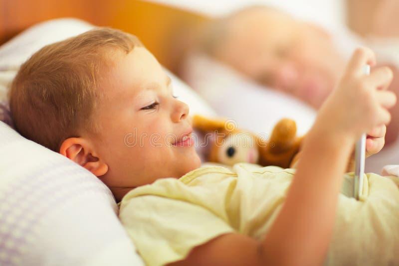 Het leuke jongen liggen op het bed en gebruikt de telefoon stock afbeeldingen