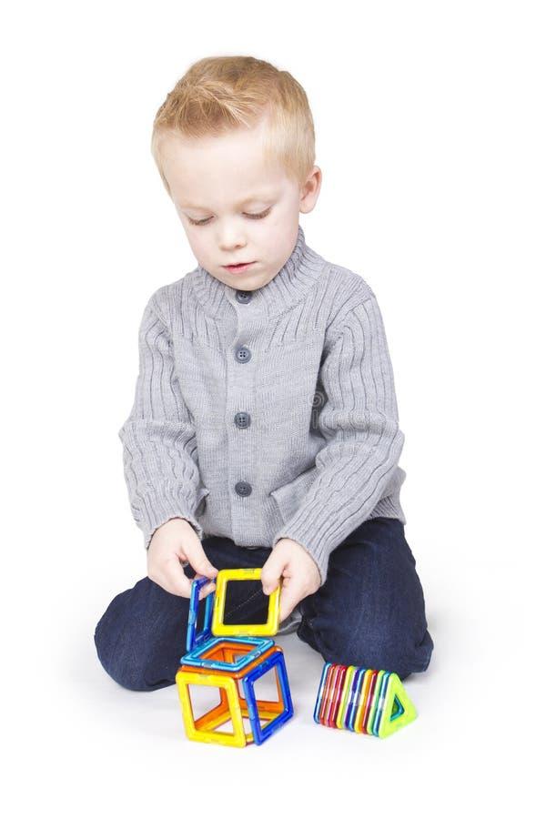 Het leuke Jongen spelen met blokken en vormen stock foto