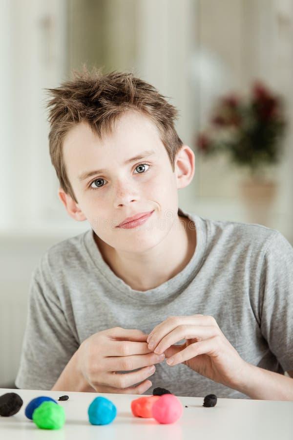 Het leuke jongen spelen met kleurrijke klei stock foto's