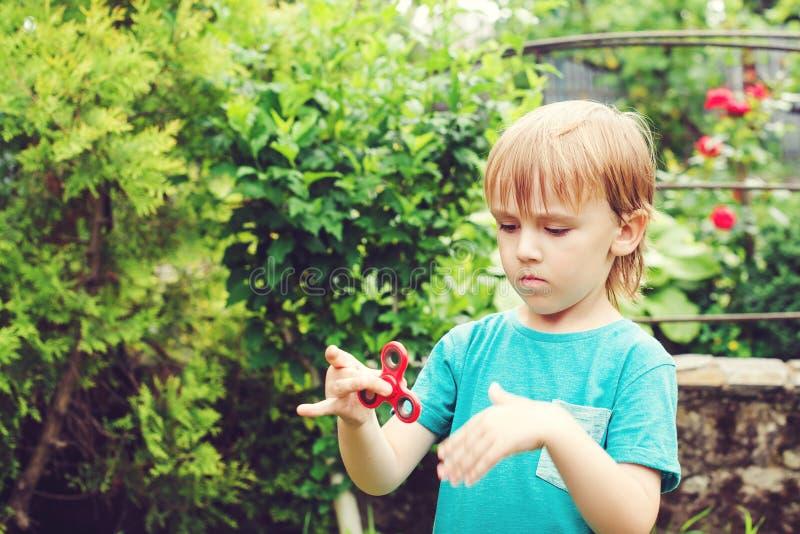 Het leuke jongen spelen met Tri friemelt in openlucht Handspinner In stuk speelgoed voor handen voor kinderen en volwassenen royalty-vrije stock foto