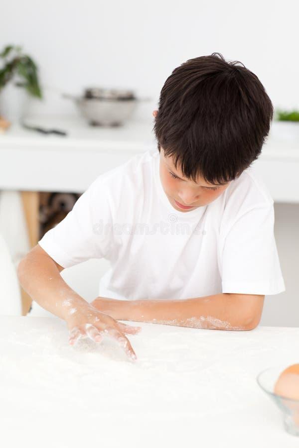 Het leuke jongen spelen met vloer terwijl alleen het koken stock foto