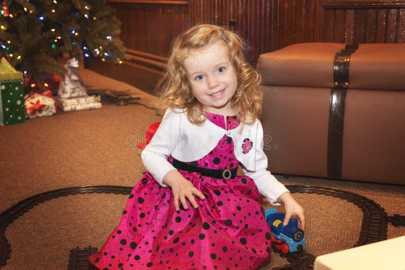 Het leuke Kaukasische blonde krullende haarmeisje speelt met een treinstuk speelgoed binnen royalty-vrije stock foto