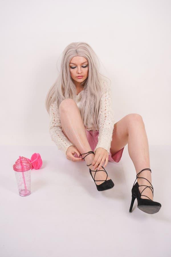 Het leuke Kaukasische jonge blondemeisje in een gebreide sweater zit op de vloer en draagt hoge hiel zwarte schoenen op haar voet stock foto