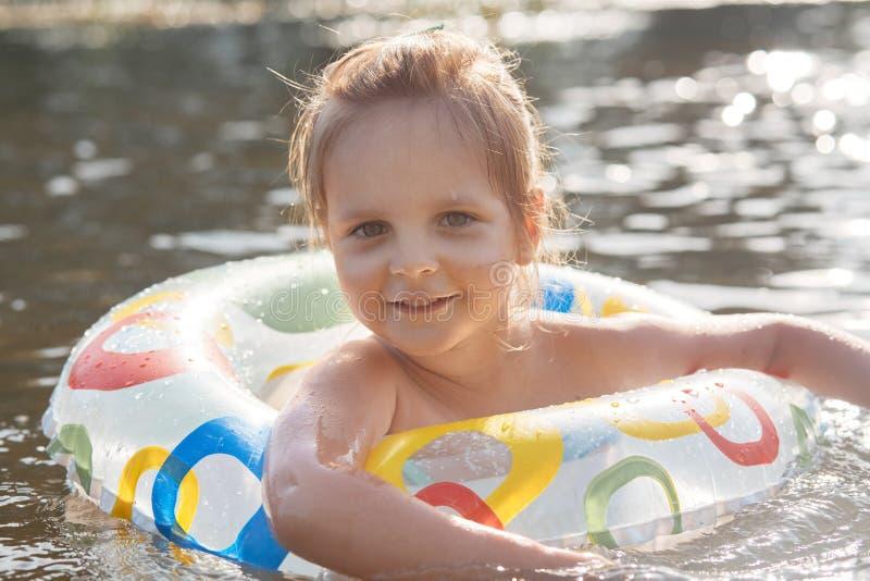 Het leuke Kaukasische kindmeisje spelen in water met opblaasbare ring, het besteden de zomertijd met pret en geluk, kind het kijk stock afbeelding