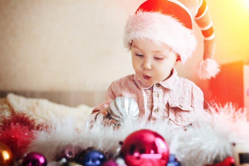 Het leuke kind in gnoomhoed verraste het kijken op een Kerstboomdecoratie, thuis stock afbeeldingen
