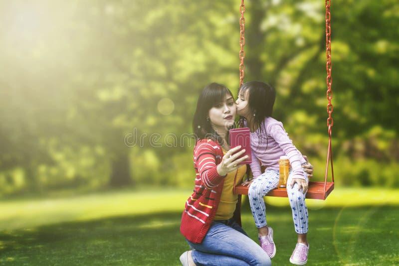 Het leuke kind kust haar moeder in het park royalty-vrije stock afbeelding