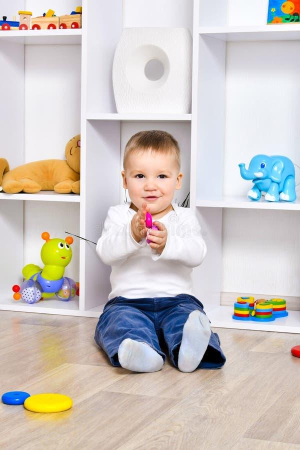 Het leuke kind spelen in de speelkamer stock foto's