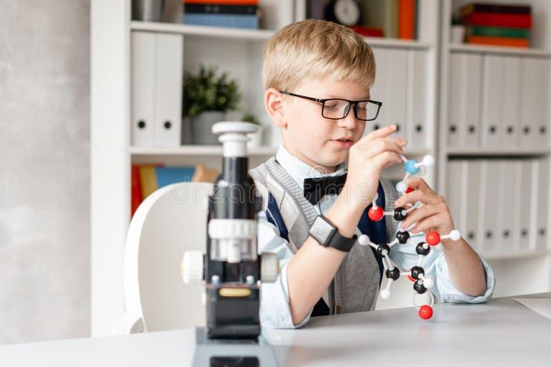 Het leuke kind in vrijetijdskleding assembleert een model van een chemisch element royalty-vrije stock fotografie