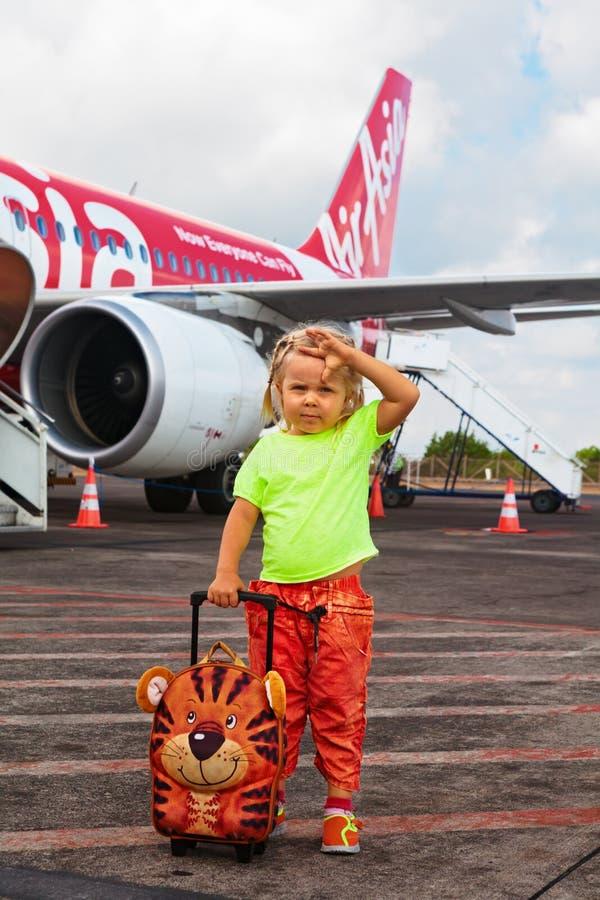 Het leuke kind wacht op het inschepen aan vliegtuig in de Internationale luchthaven van Bali stock afbeelding
