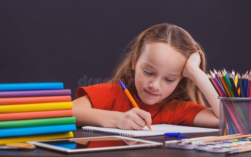 Het leuke kind zit binnen bij een bureau Het jonge geitje trekt in klasse op achtergrond van bord stock foto's